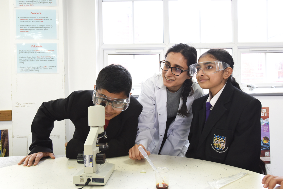 two students and a teacher looking at a microscope